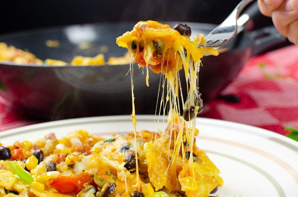Breakfast Brunch Nacho's with  gooey melted cheese on a silver fork being served on a white plate