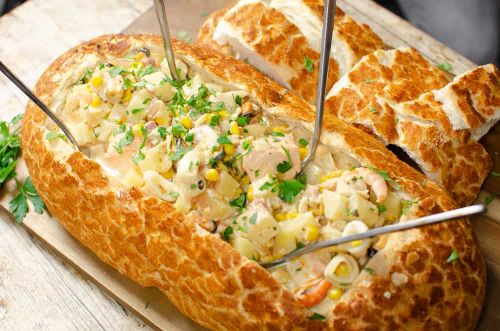 Fish chowder in a bread boat with silver spoons int he fish chowder