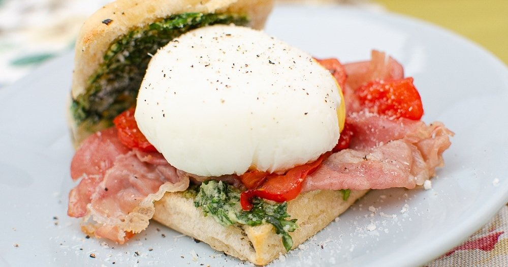 Poached double yolk egg with pesto tomato and prosciutto in a Focaccia Roll Parmesan & Basil Pesto