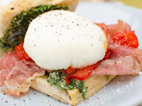 poached double yoak egg with pesto tomato and prosciutto in a Focaccia Roll