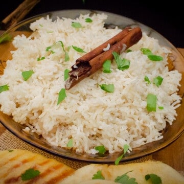Onion Basmati Rice in a glass bowl with chopped coriander and a cinnamon stick on top