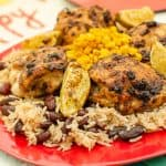 Jerk chicken with rice,beans and fried sweetcorn served on a red plate