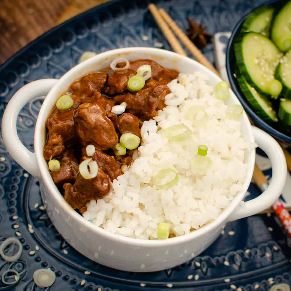 Korean Beef with rice in a white bowl on a blue plate with chop sticks and  cucumber on the side