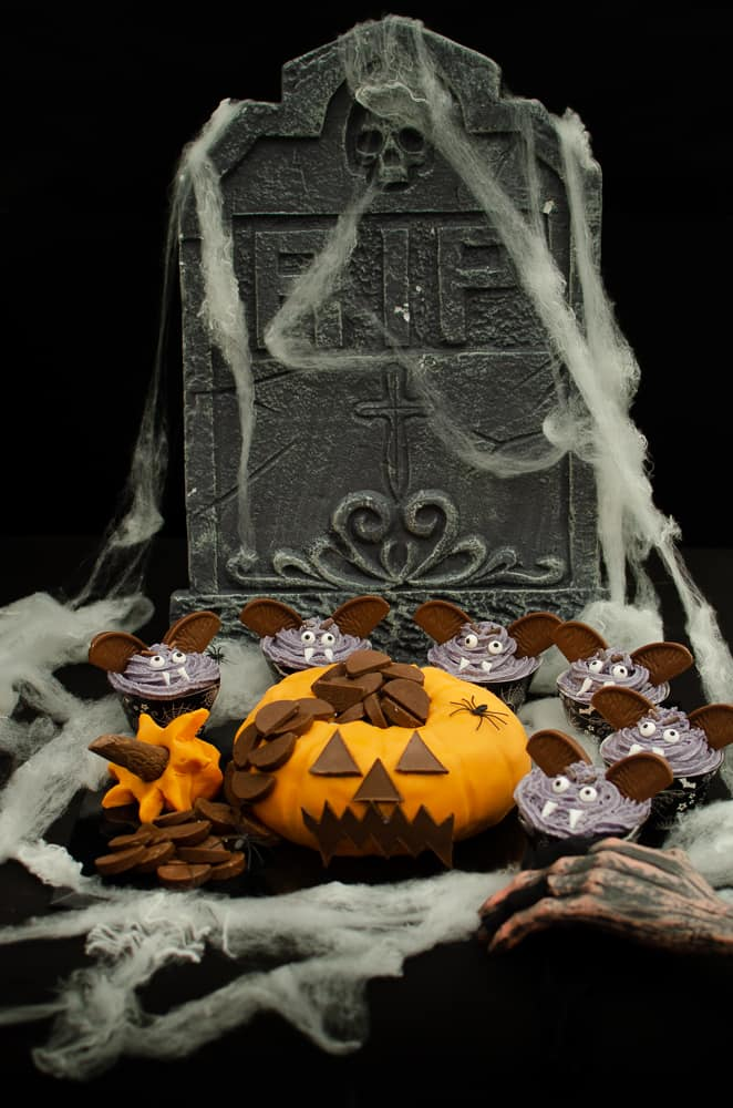 Terry's Chocolate Orange pumpkin cake surrounded by vampire cupcakes with cobwebs and a zombie hand