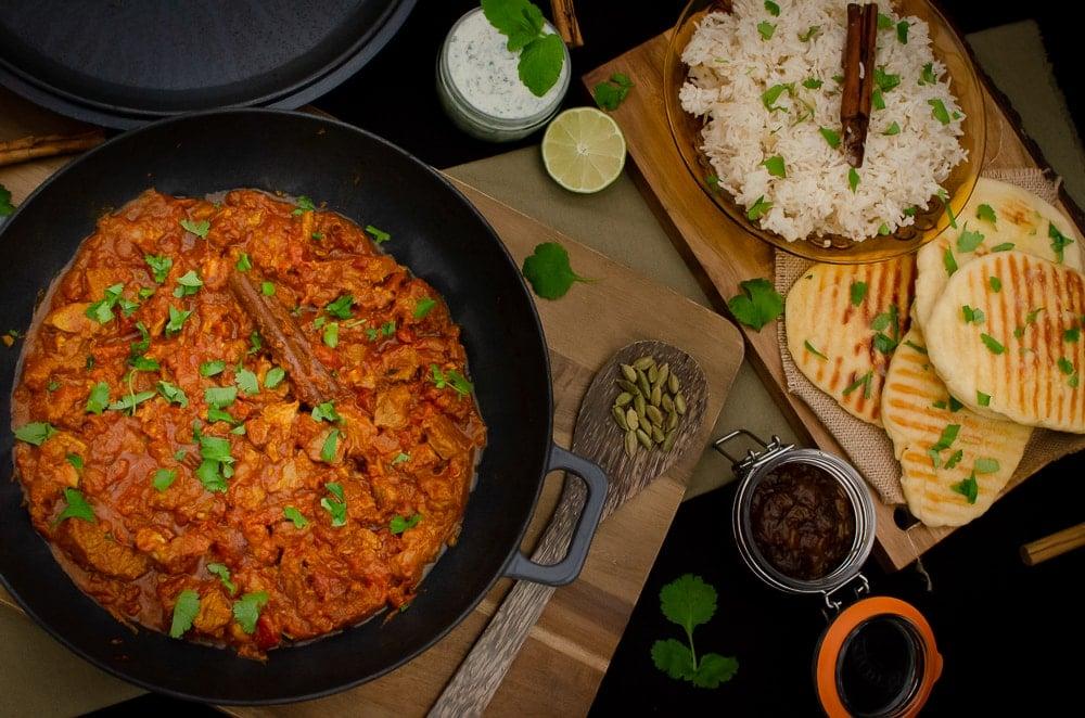 Homemade Lamb curry with mango chutney, raita, garlic naan and onion basmati rice served on wooden chopping boards
