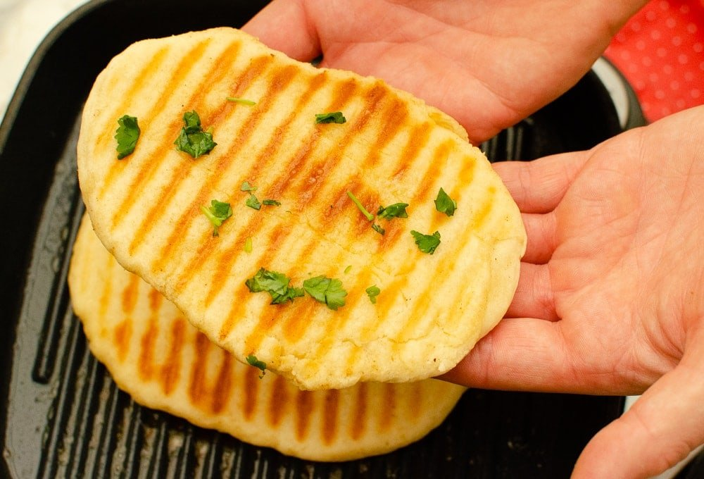 Homemade Garlic Naan Bread being held up by Luke from Flawless food after just being cooked on a skillet