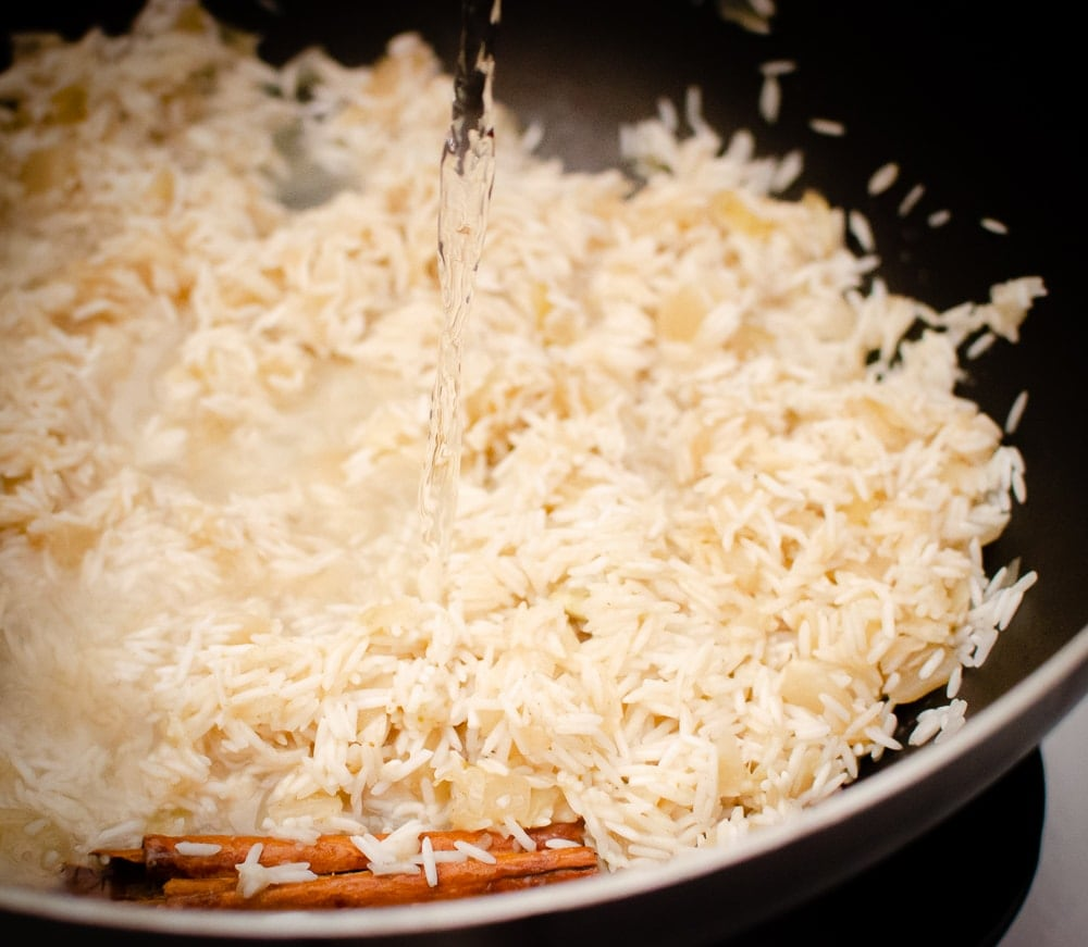 Water being poured over the rice, onions and spices in a black pan