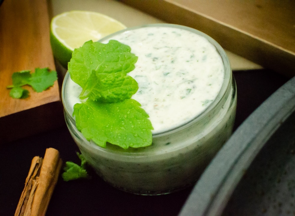 Cucumber and Mint Raita in a glass dish with fresh mint leaves, wedge of lime and a cinnamon stick