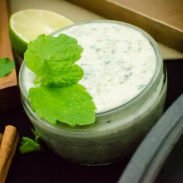 Cucumber and Mint Raita in a glass jar with mint leaves on top