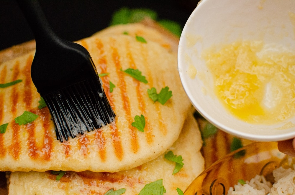 Spreading Garlic butter over the naan bread with a black rubber brush
