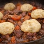 Beef and Red wine stew with Dumplings in a cast iron dish with homemade bread and fresh vegetables
