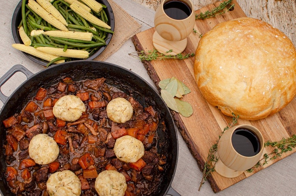 Beef and Red wine stew with Dumplings in a cast iron dish with Homemade bread on the side with two cups of red wine and fresh vegetables on a black plate