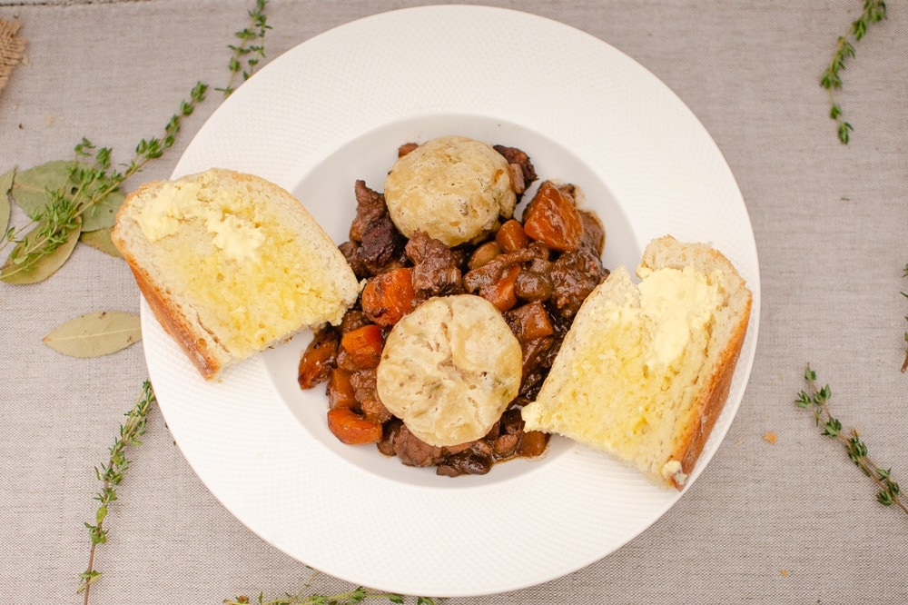 Beef and Red wine stew with Dumplings in a white bowl next fresh homemade bread
