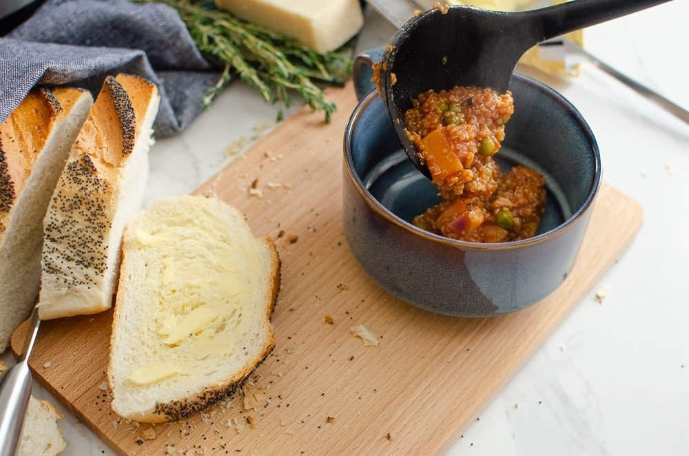vegetable stew being served into a blue bowl on a bread board next to buttered crusty bread