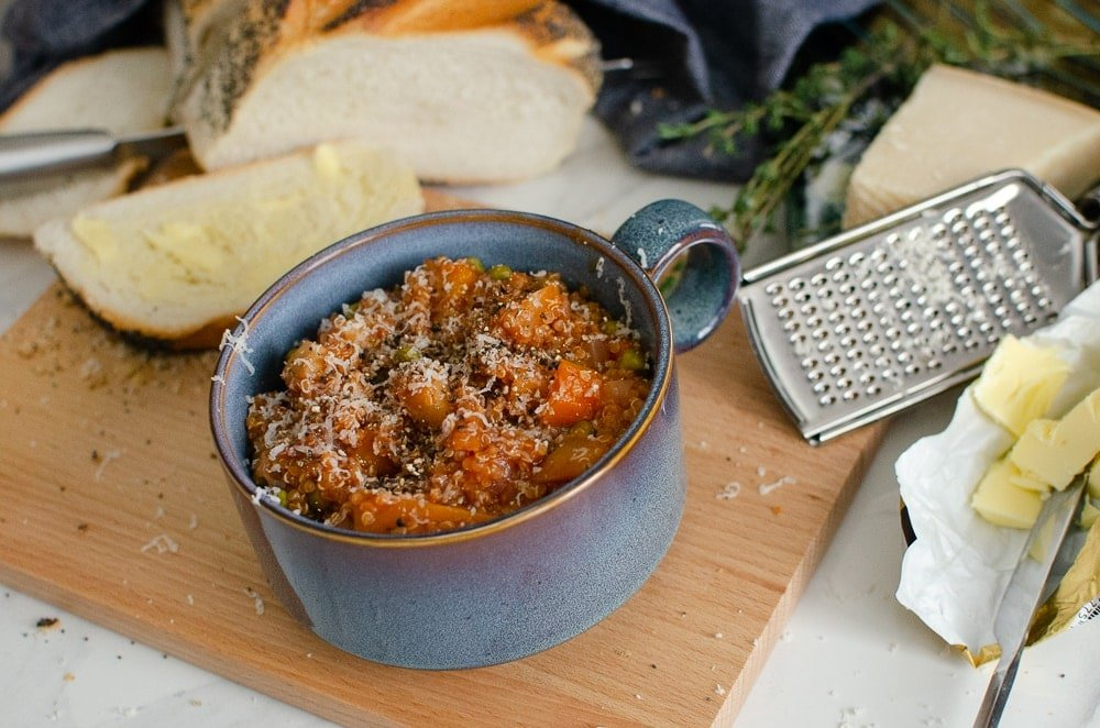 Quinoa vegetable stew in a blue bowl on a bread board next to buttered crusty bread and Parmesan cheese with grater