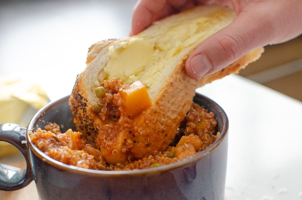 crusty bread being dipped into vegetable stew in a blue bowl on a bread board