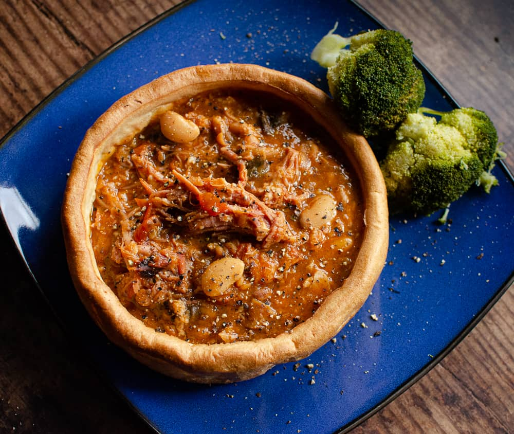 Bonfire Gammon stew in a Giant Yorkshire Pudding with Broccoli on a blue plate