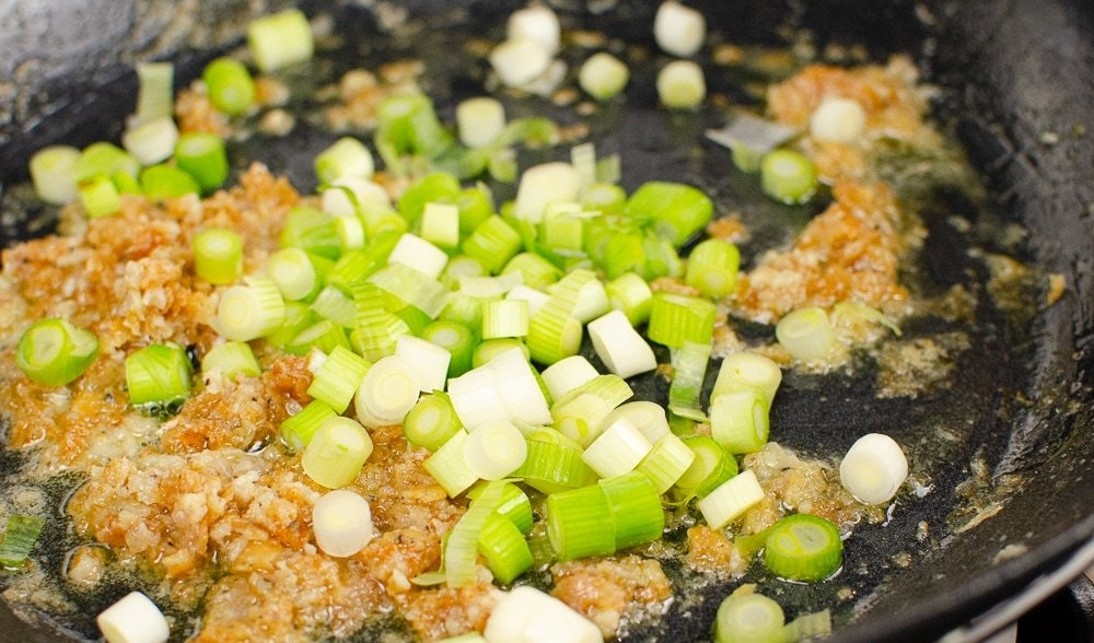 chopped spring onions in a pan cooking our sizzling spicy pork