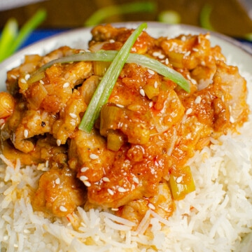sizzling spicy pork served on white rice in a white bowl