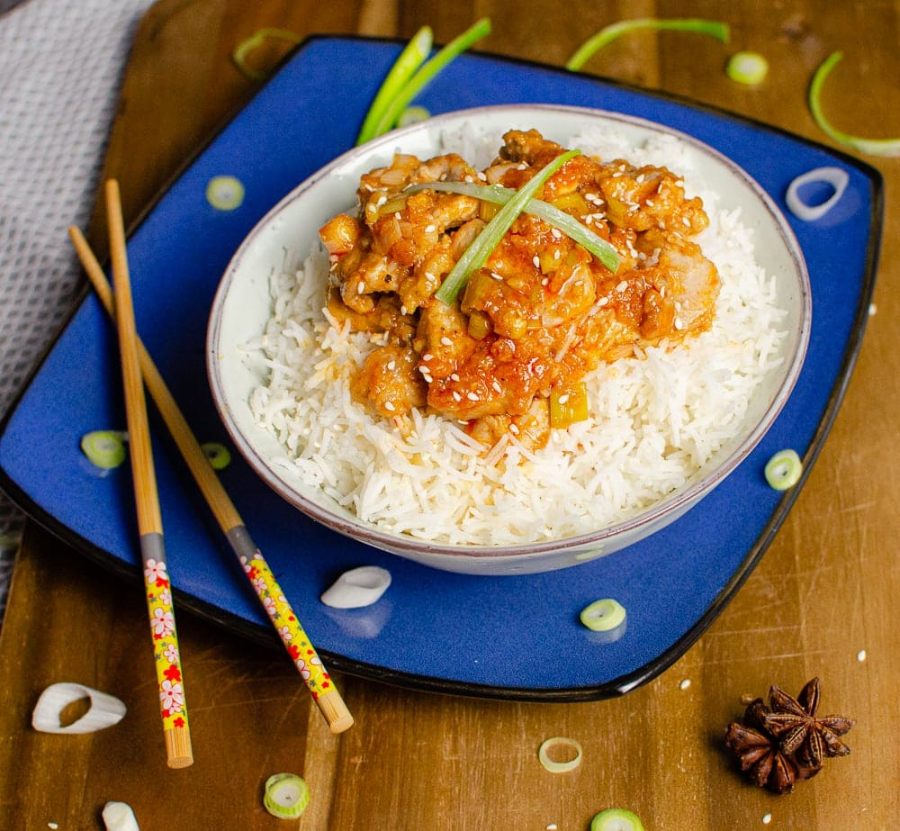 sizzling spicy pork served in a bowl with white rice on a blue plate with chopsticks,onions and star anise on the side