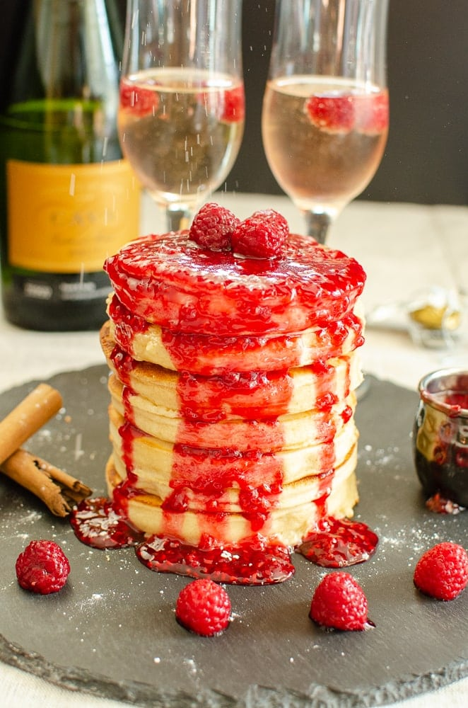 Stack of Bubbly Pancakes, Raspberry sauce with champagne, cava , brut, in flutes with raspberries and cinnamon sticks on black slate