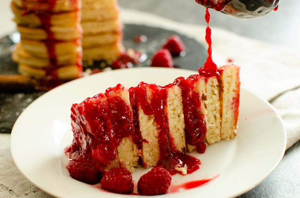 Raspberry Sauce With Champagne in a small silver sauce pot sitting next to a stack of Bubbly Pancakes