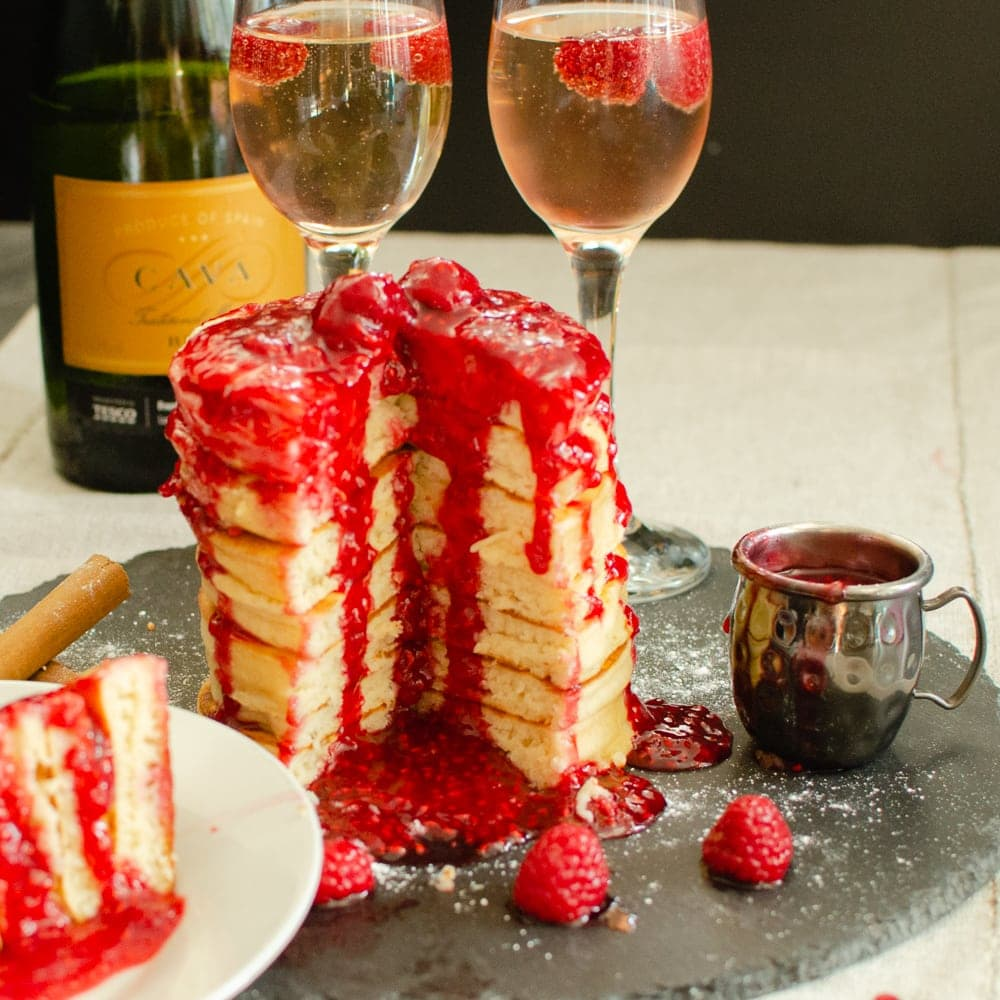 stack of Bubbly Pancakes covered in Raspberry sauce with champagne, cut into 1/4 segment