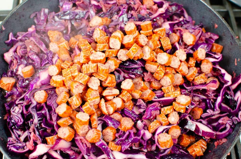 Kabonas sausage being place on the red cabbage to make our being placed on the Red cabbage with Apple and Kabonas