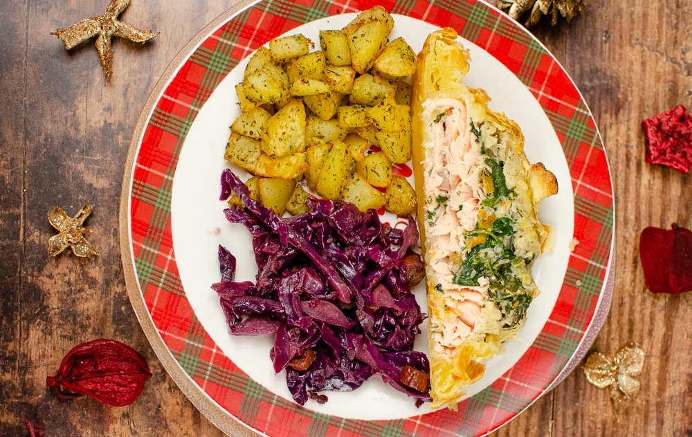 Salmon en croute served with red cabbage and potatos on a white and tartan plate
