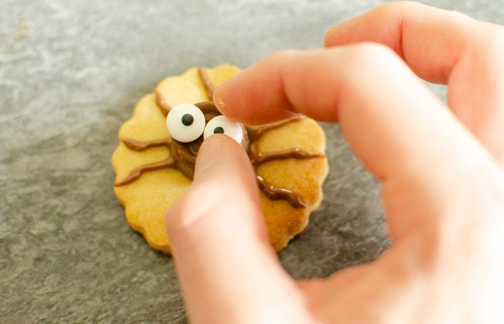 adding eyes to spider body Cute Spider Halloween Biscuit's on marble worktop
