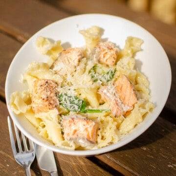 salmon pasta with cream white wine and spinach in a white bowl next to knife and fork