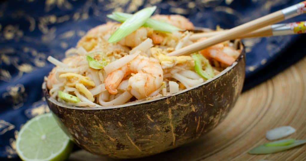 Pad Thai noodle prawns in a coconut shell bowl