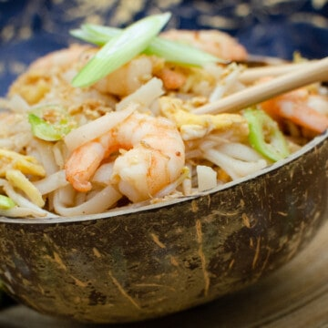 Pad Thai noodle prawns in a coconut shell bowl with chopsticks on blue towel