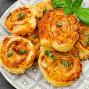 Sundried Tomato Bacon and Mozzarella Swirls served up on a plate with basil
