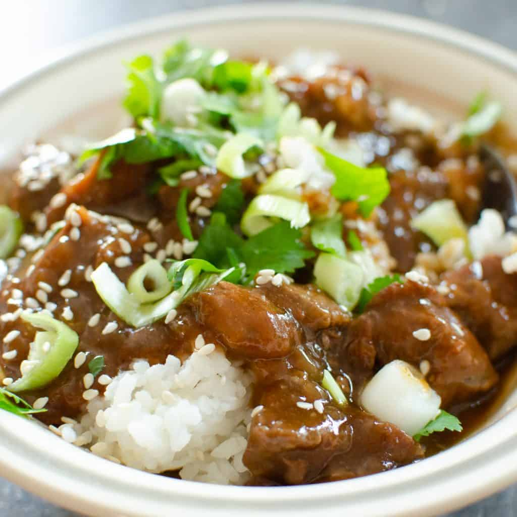 Korean beef served with white rice sprinkled with spring onions and sesame seeds in a white bowl