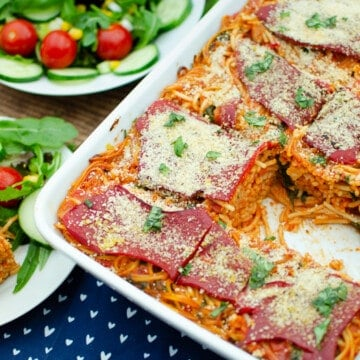Sundried Tomato and Roasted Pepper Pasta in a white oven dish and on the side its served on a white plate with salad