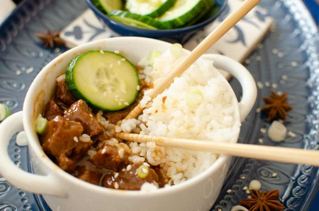 Korean Beef with rice in a white bowl on a blue plate with chop sticks inside the bowl with cucumber and star anise  on the side