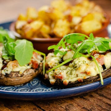Pancetta mushrooms with mozzarella on a blue plate served with rocket salad and potato squares