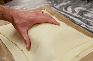 Placing puff pastry top over the salmon and cream cheese filling to make a parcel
