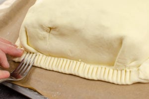 Crimping the edges of the salmon en croute with a silver fork