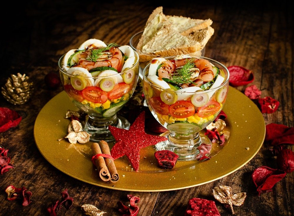 Smoked Salmon Cocktail Recipe served in glass bowls layers of cucumber, sweetcorn, tomatoes, olives, egg, smoked salmon and wholemeal bread on gold plate festive starter