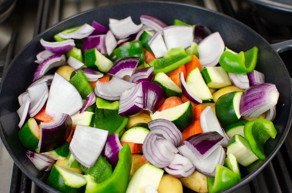 Cut up vegetables in a cast iron pan to make Croatian peka