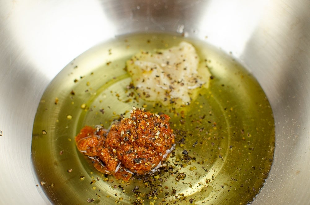 olive oil, gia sundried tomato puree and gia garlic puree and black pepper in a silver bowl