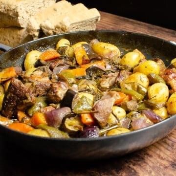 Croatian Lamb Peka in a cast iron dish on a wooden table with bread to serve