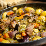 Croatian lamb peka with potatoes,peppers and herbs in a cast iron pan on a wooden table