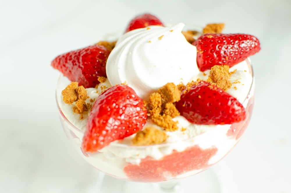 Crushed biscuit placed on top of the cream in a glass to create our Eton mess dessert