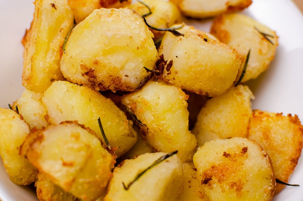 Roast Potatoes with rosemary herb in a white bowl