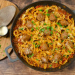 one pot spicy meatball pasta in a cast iron dish seasoned with Parmesan and chopped parsley