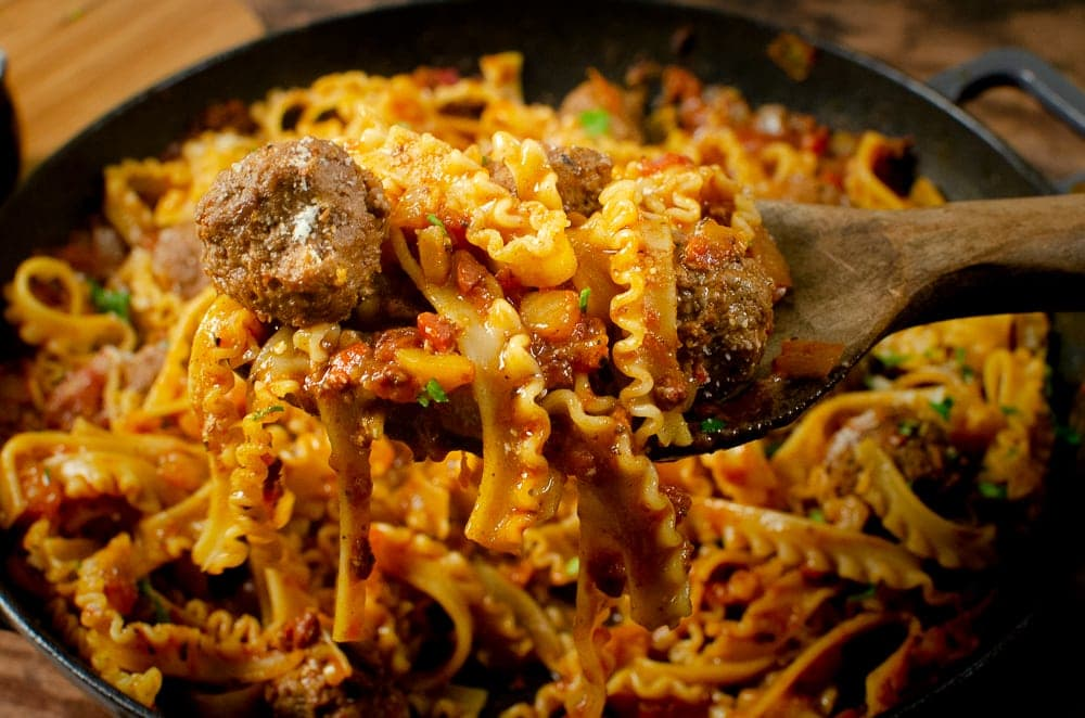 one pot spicy meatball pasta recipe in a cast iron dish seasoned with Parmesan and chopped parsley being served with a wooden spoon