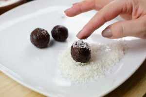 Rolling our dark chocolate truffles in coconut sprinkles on a white plate